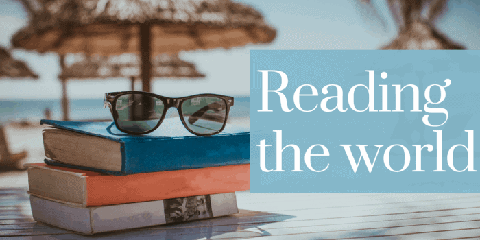 Reading the world banner - A pile of books on the beach; a pair of sunglasses on top of the pile of books