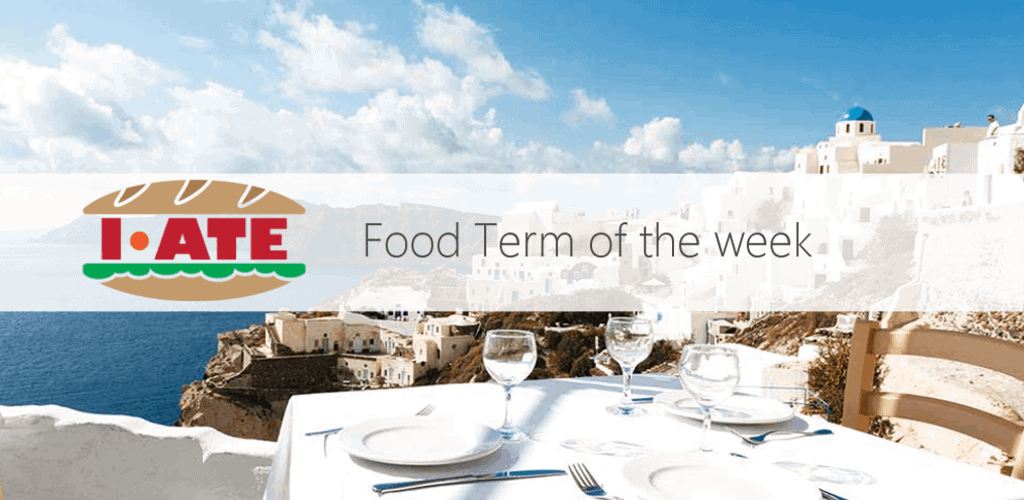 I-ATE Food Term of the Week banner - Served table with white tablecloth against blue water of Aegean sea on Santorini island resort in Greece, Europe.