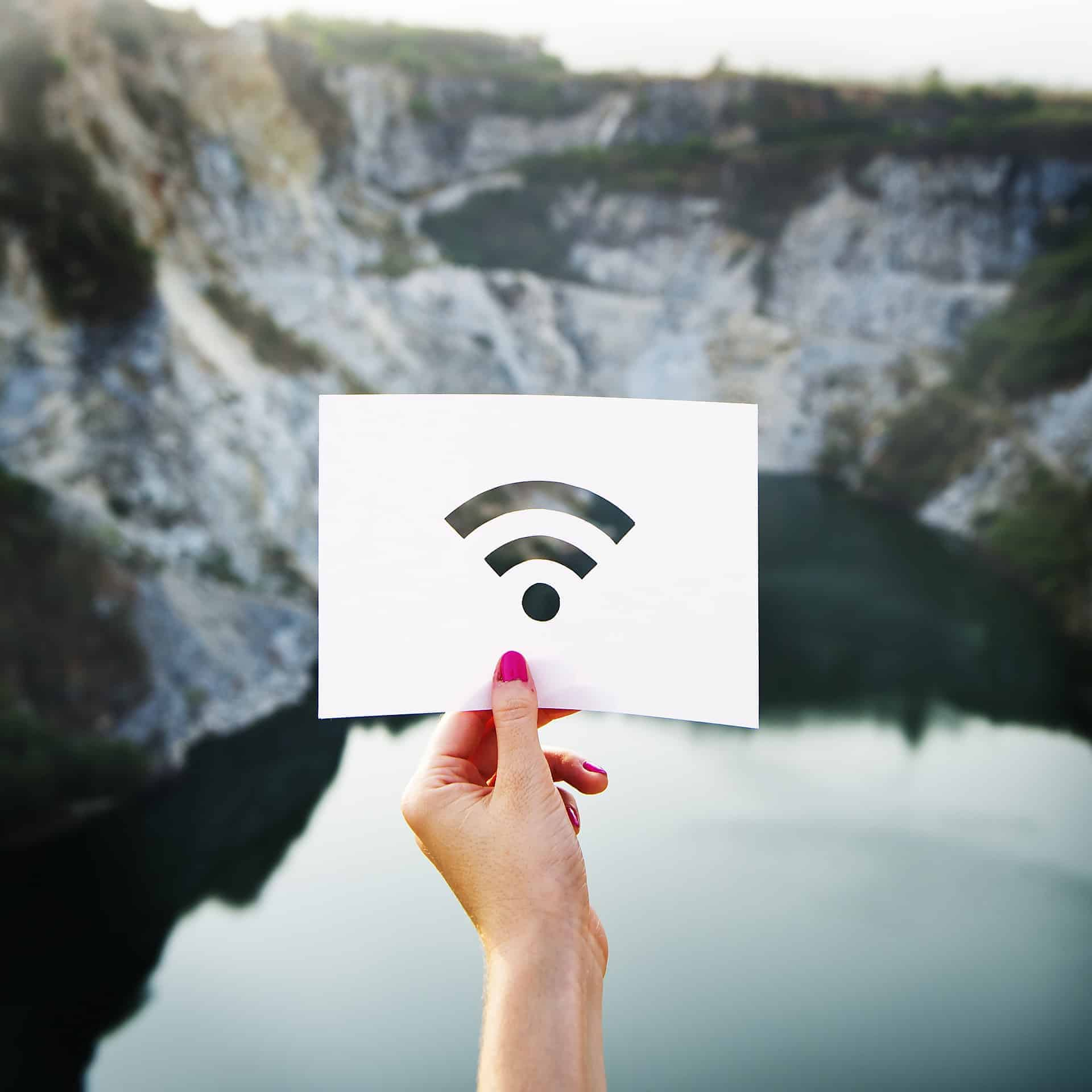 Woman holding the Wi-Fi signal; background of a cliff